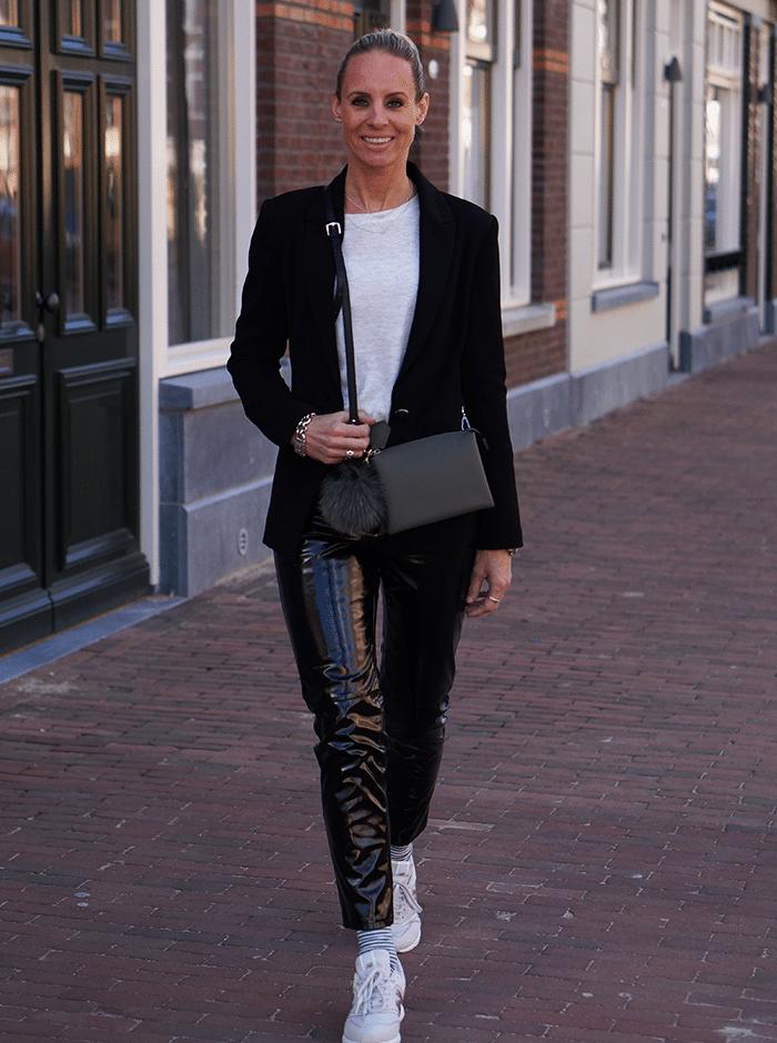 Lakleren broek op een beige top met zwarte blazer