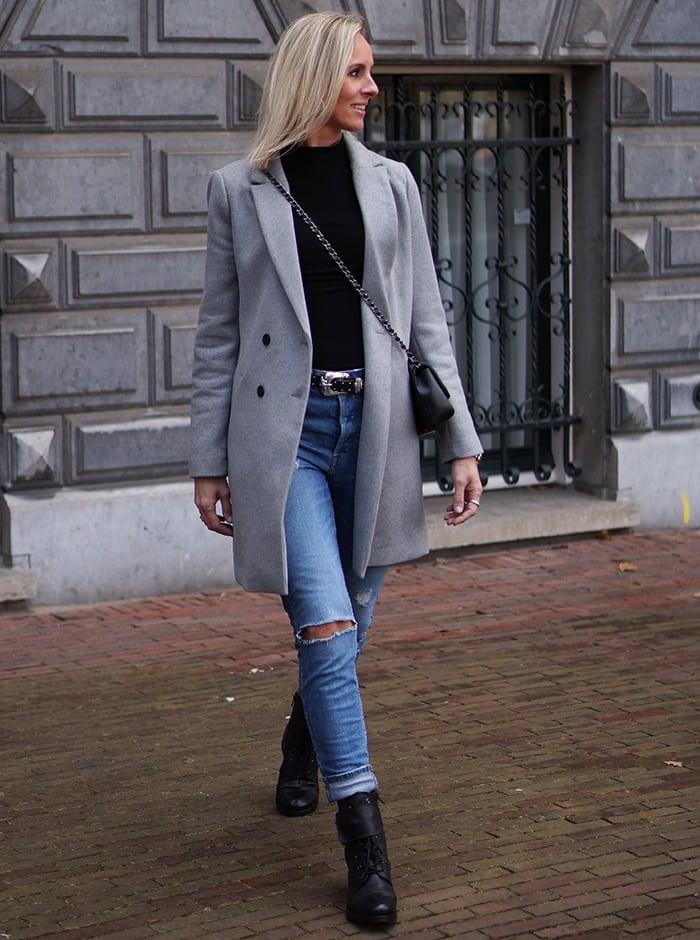 Jeans, zwarte laarsjes en top, gecombineerd met grijze jas